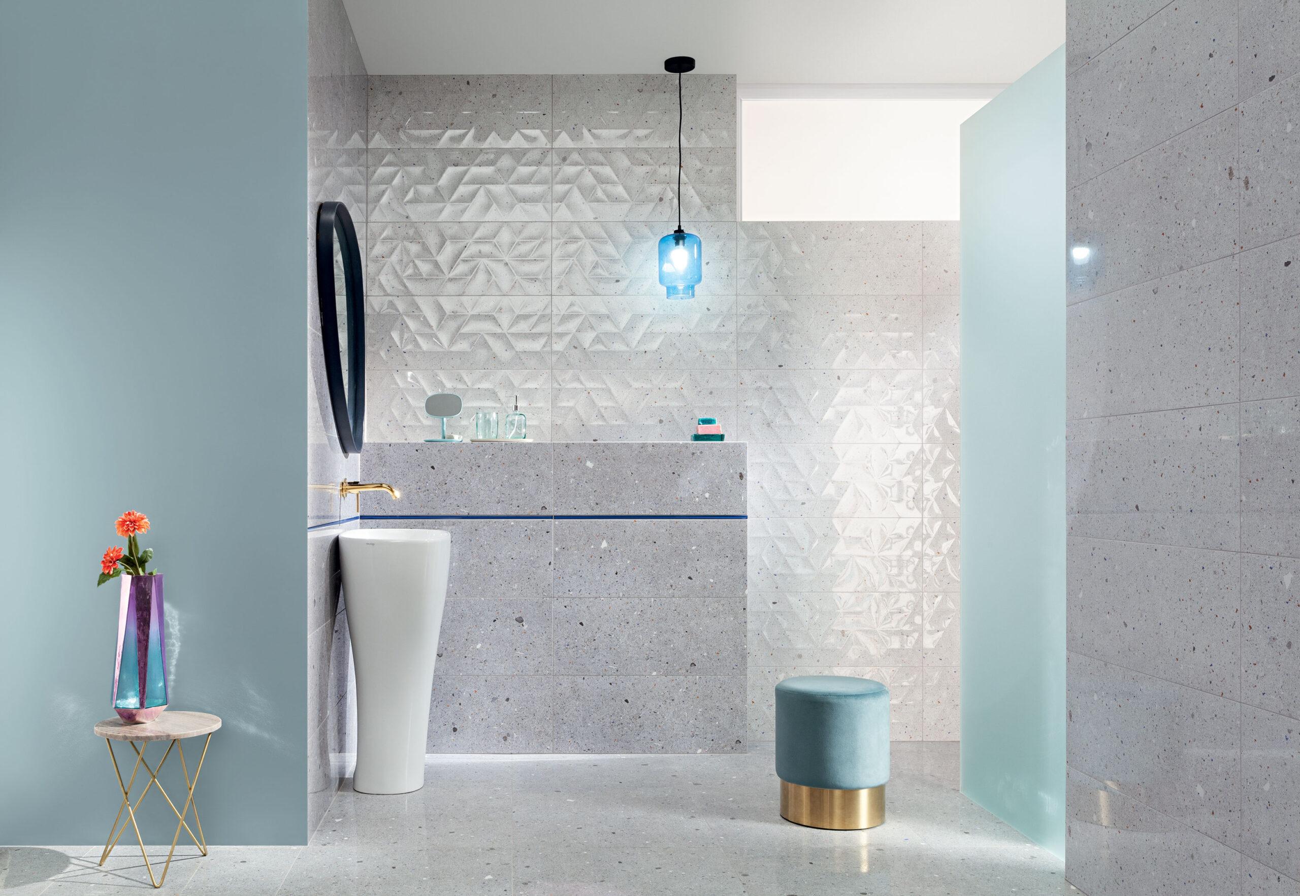 Szara łazienka z ozdobnymi i kolorowymi wzorami na płytkach.